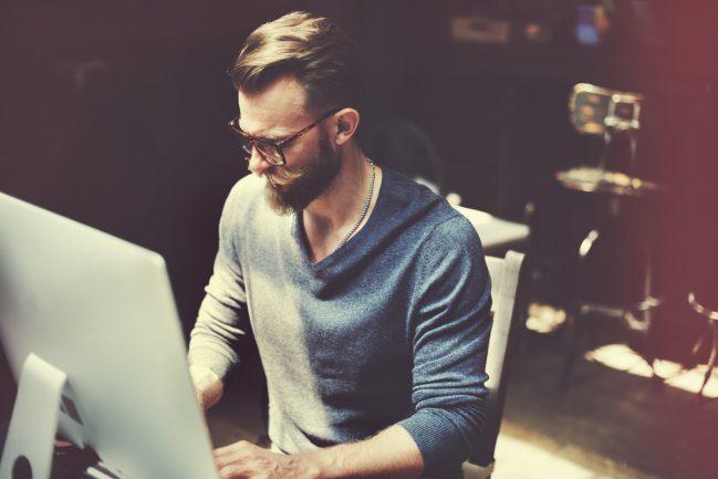 Mann sitzt vor seinem Computer und arbbeitet für die digitale Wirtschaft
