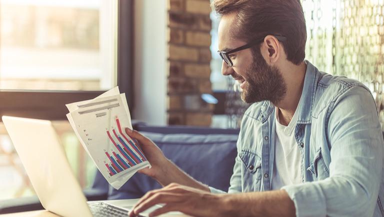 Man betrachtet Kurven und Statistiken seiner Einnahmen im Internet über Affiliatelinks