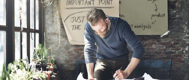 Mann beginnt zu planen und zu machen, statt der Prokrastination zu verfallen.