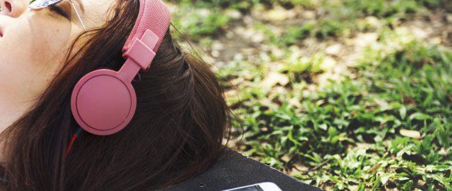 Skatergirl liegt in einer Wiese und hört schöne Musik.